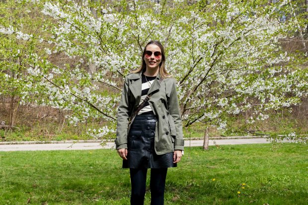 Look da Giuli Castro com trench coat verde militar, malha de listras, saia de couro de botões, meia-calça e tenis